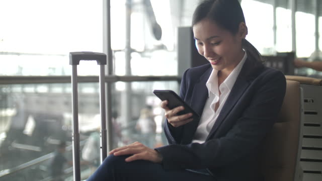 businesswoman using smart phone at airport - thai culture stock videos & royalty-free footage