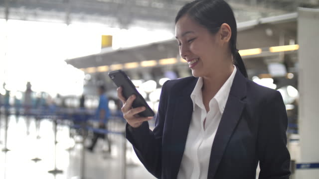 businesswoman using smart phone at airport - business travel stock videos & royalty-free footage