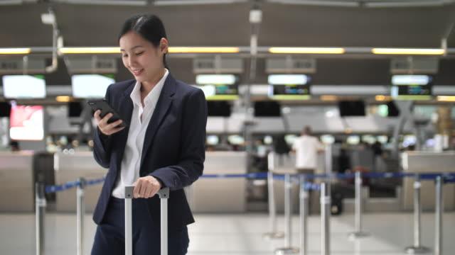 空港でスマートフォンを利用するビジネスウーマン - ロビー点の映像素材/bロール