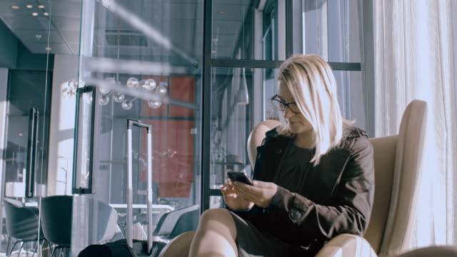 vídeos y material grabado en eventos de stock de ms businesswoman usando teléfono inteligente en el vestíbulo del hotel - sillon