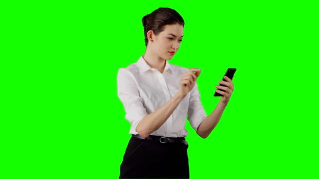 Businesswoman using smart phone on a green screen