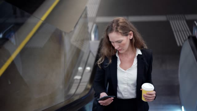 businesswoman using smart phone - escalator stock videos & royalty-free footage