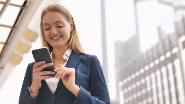 donna d'affari che usa lo smartphone - dispositivo informatico portatile video stock e b–roll