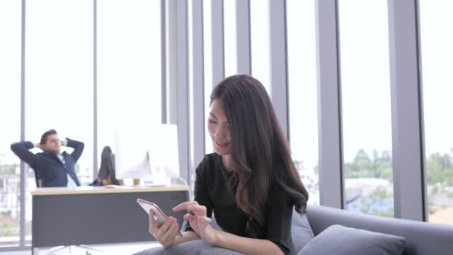 実業家は、スマート フォンを使用します。アジアの若い実業家がスマート オフィスでリラックスします。 - 受ける点の映像素材/bロール