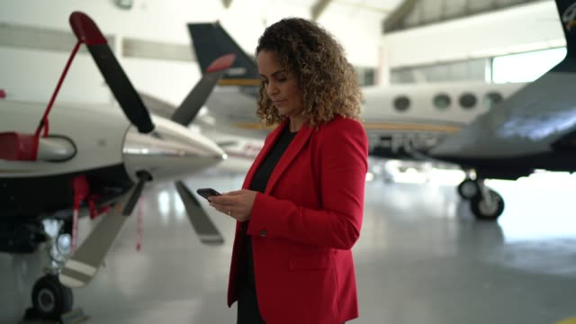 businesswoman using smartphone in a hangar - airplane hangar stock videos & royalty-free footage