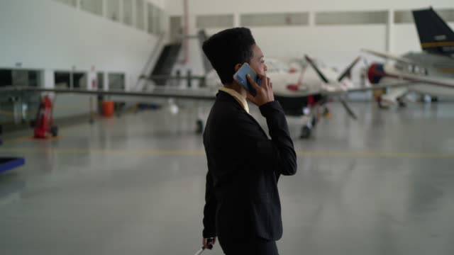 vídeos de stock e filmes b-roll de businesswoman using smartphone in a hangar - perfil vista lateral