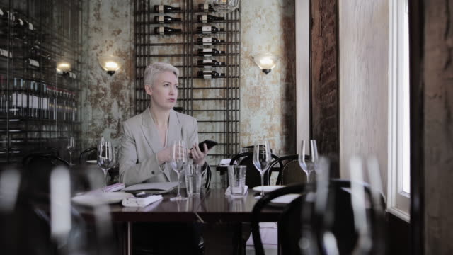 vidéos et rushes de businesswoman using smartphone in a restaurant - déjeuner