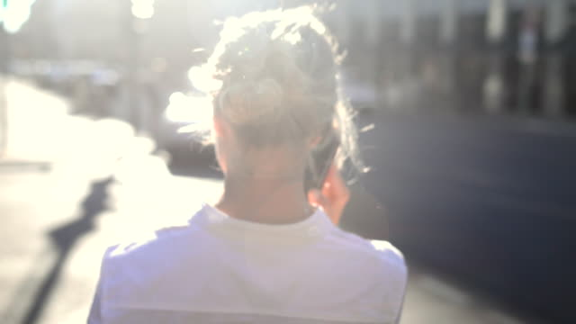 businesswoman using smartphone in sunlight. - millennial generation stock videos & royalty-free footage