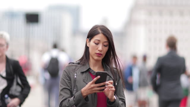 Businesswoman using smartphone on crowded street