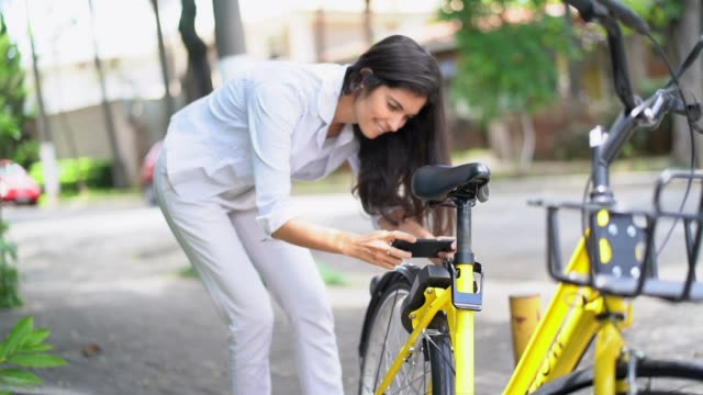 Businesswoman using smartphone scanning the QR code of shared bike in city