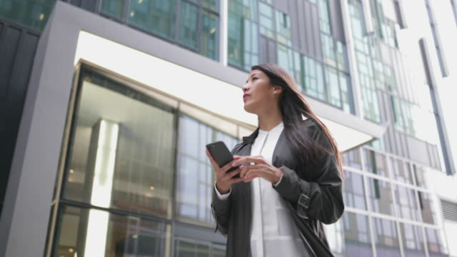 businesswoman using smartphone walking in city - brown hair stock videos & royalty-free footage
