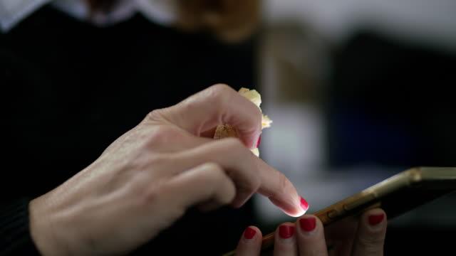 おやつを食べながらスマート フォンを用いた cu 実業家 - 食べ物 サンドイッチ点の映像素材/bロール