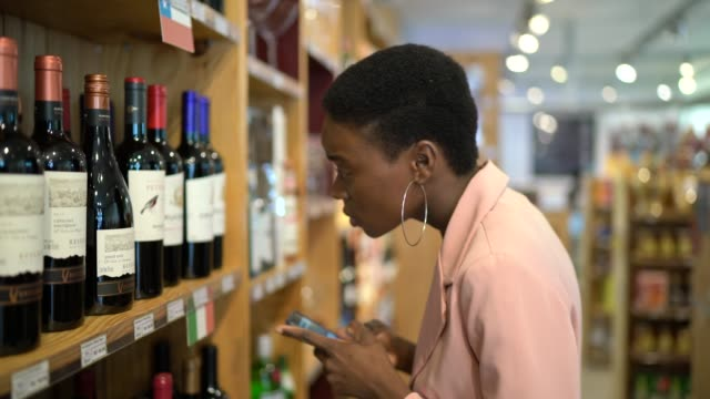 businesswoman using smartphone while shopping in a supermarket - wine stock videos & royalty-free footage