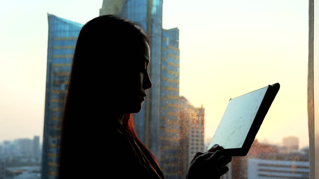businesswoman using tablet near the window at sunset period. - back lit woman stock videos & royalty-free footage