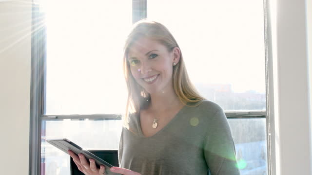 Businesswoman using tablet PC in brightly office