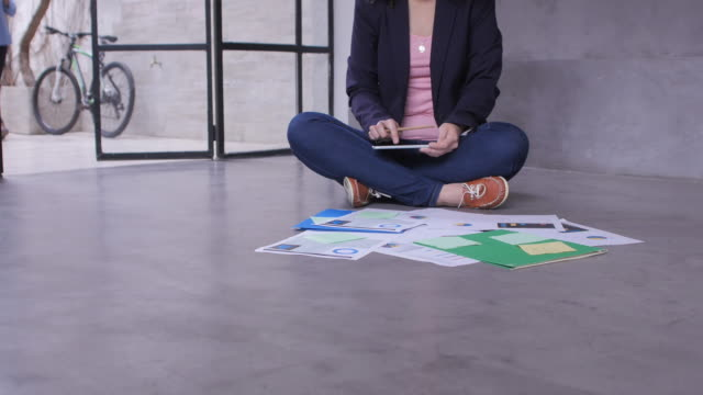 Businesswoman using tablet pc on floor in office