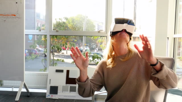 MS Businesswoman using virtual reality headset in office