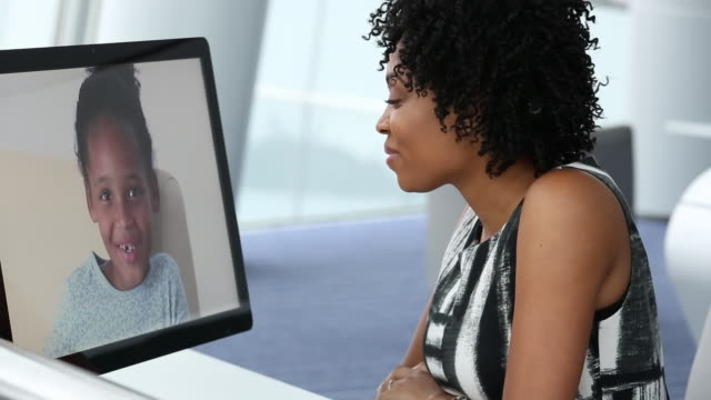 MS DS Businesswoman Video Conferencing with Young Daughter on Computer While in Corporate Office / Virginia Beach, Virginia, United States