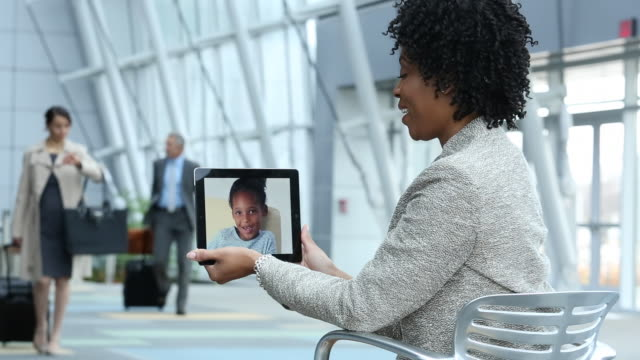 MS Businesswoman Video Conferencing with Young Daughter  on Tablet Computer in Airport Lobby / Virginia Beach, Virginia, United States