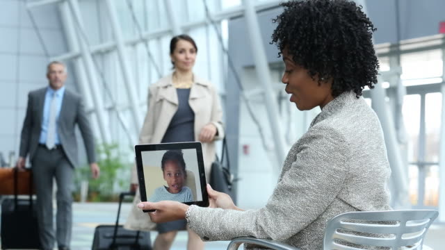 ms businesswoman video conferencing with young daughter  on tablet computer in airport lobby / virginia beach, virginia, united states - berufstätige mutter stock-videos und b-roll-filmmaterial