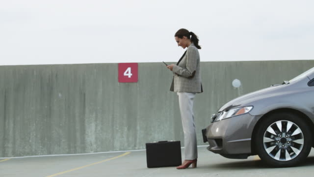 Businesswoman waiting by car in car park