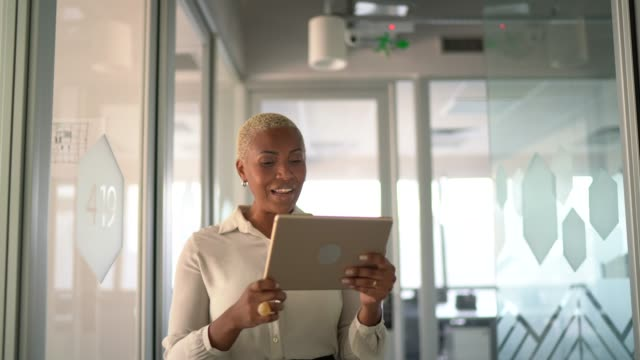 businesswoman walking and doing a video call on digital tablet at work - short hair stock videos & royalty-free footage