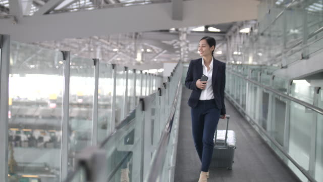 businesswoman walking and using smart phone at airport, business travel - pulling stock videos & royalty-free footage