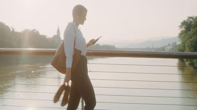 vidéos et rushes de femme d'affaires de ms marchant pieds nus à travers un pont dans la ville - cheveux courts