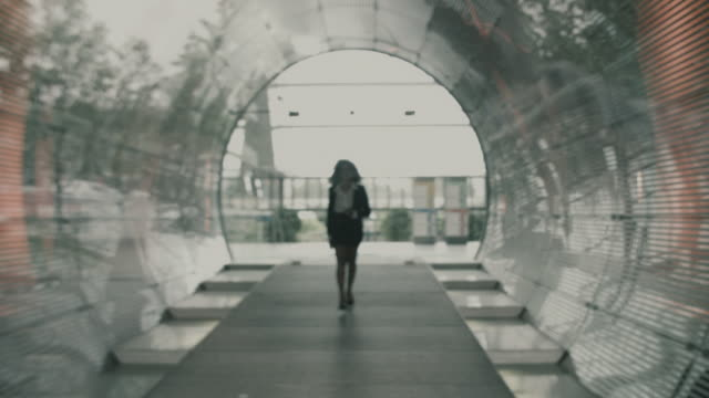 Businesswoman walking down corridor, leaving building