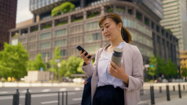 スマートフォンを使い、再利用可能な水筒を持ちながら通りを歩くビジネスウーマン - 最高経営責任者点の映像素材/bロール