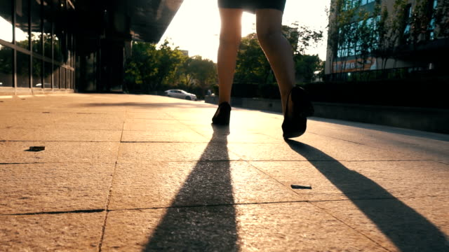 Businesswoman walking in the urban street at sunset