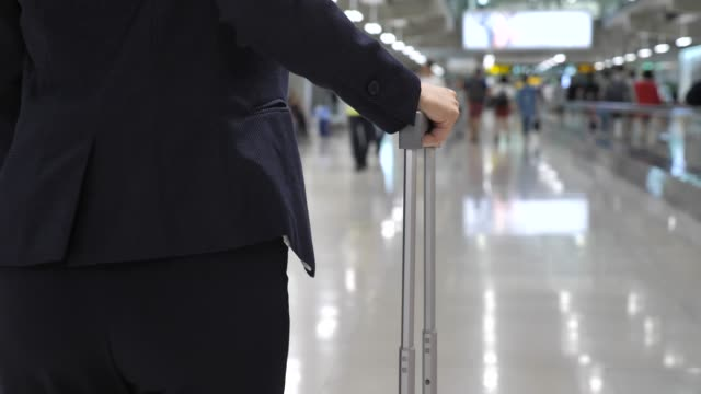 businesswoman walking on airport and roll suitcase - wheeled luggage stock videos and b-roll footage
