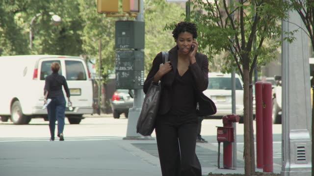 MS Businesswoman walking on street using mobile phone, smiling / New York City, New York, USA.