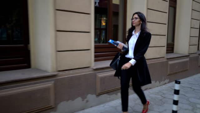 Businesswoman walking on the street with paper files and journals in hand.