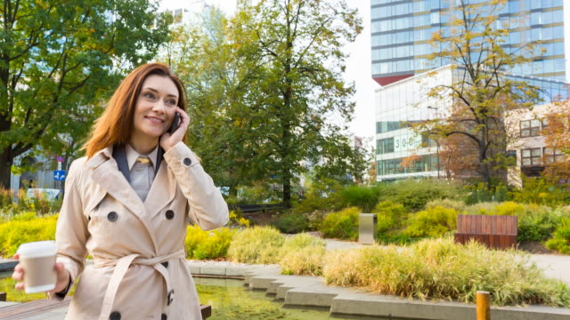 businesswoman walking outdoors with coffee and mobile phone - ruhen stock-videos und b-roll-filmmaterial