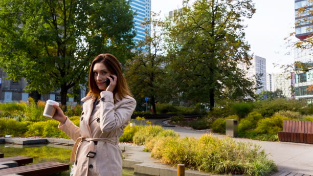 Businesswoman walking outdoors with coffee and mobile phone