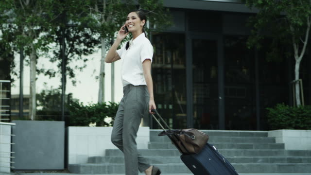 MS of businesswoman walking outdoors with mobile phone