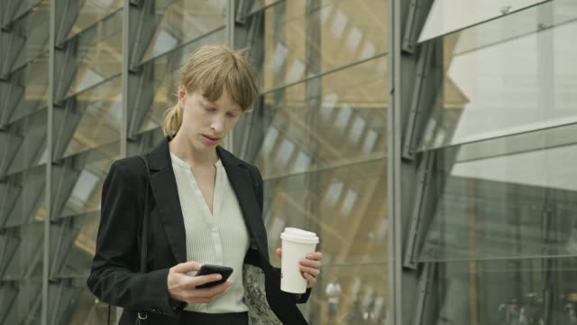 businesswoman walking outdoors with smart phone and coffee - full suit stock videos & royalty-free footage