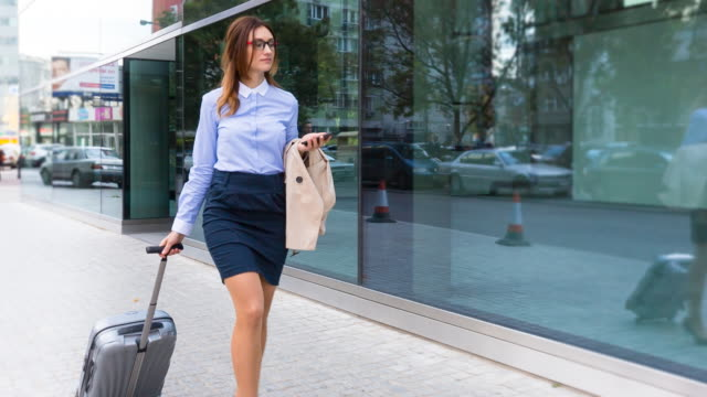 CU Businesswoman walking outdoors with trolley