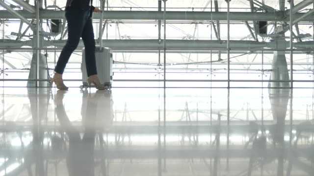 businesswoman walking rolling luggage in airport terminal, business travel - suitcase stock videos & royalty-free footage