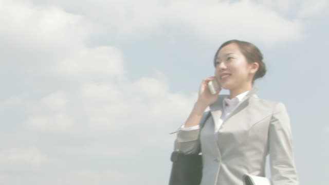 Businesswoman walking talking on cellular phone
