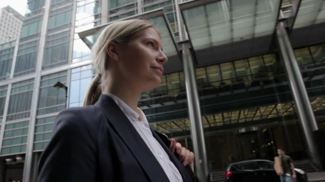 businesswoman walking through city financial district - archivista video stock e b–roll