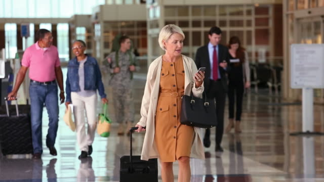 businesswoman walking through the airport video chatting