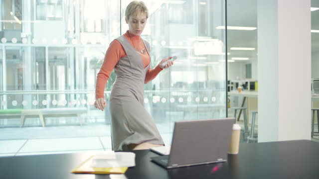 MS businesswoman walking to desk texting on cell phone