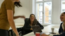 Businesswoman walking towards colleagues at desk