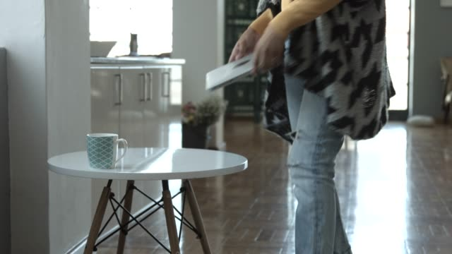Businesswoman walking towards table and using laptop