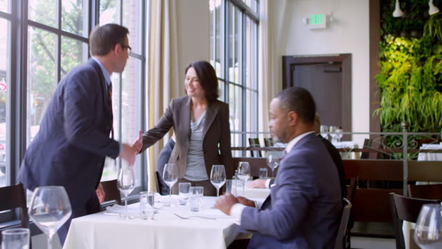 ms businesswoman walking up to table in restaurant and shaking hands with two businessmen before sitting down at table. - business lunch stock videos & royalty-free footage