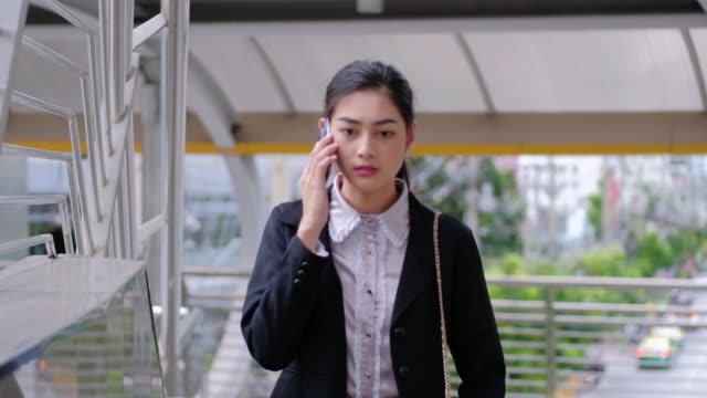 4K : Businesswoman walking using smartphone.