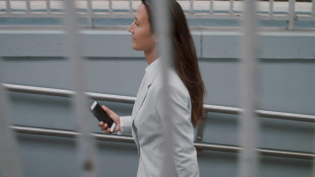 businesswoman walking with cell phone - formal stock videos & royalty-free footage