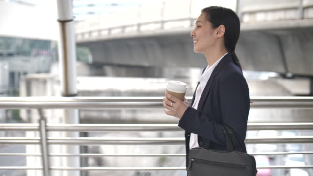 businesswoman walking with coffee cup, commuting to work - asia stock videos & royalty-free footage